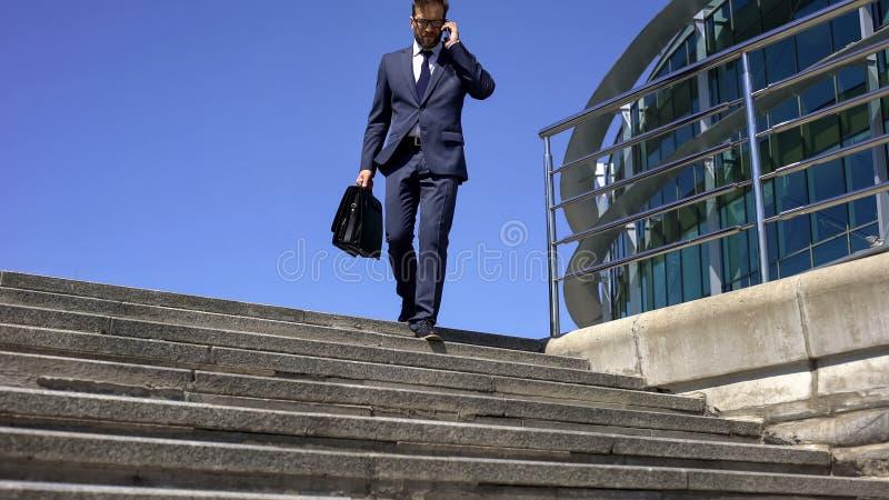 Hombre de negocios cansado con la maleta que habla en el teléfono con el socio, yendo abajo de las escaleras foto de archivo