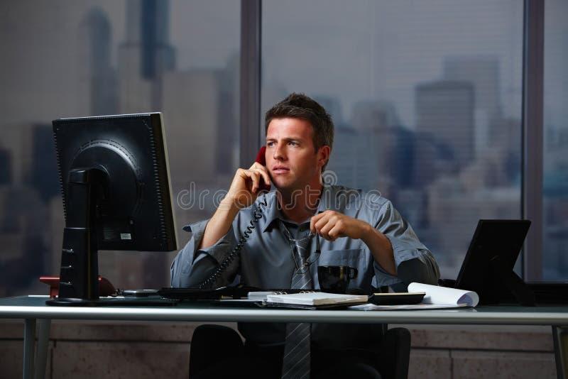 Hombre de negocios en la llamada que trabaja en horas extras foto de archivo