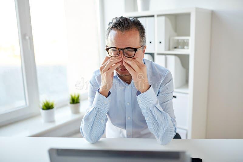 Hombre de negocios cansado en vidrios con el ordenador portátil en la oficina foto de archivo libre de regalías