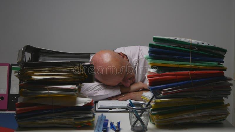 Hombre de negocios cansado Image Sleeping On el escritorio en sitio financiero de la oficina del archivo fotos de archivo