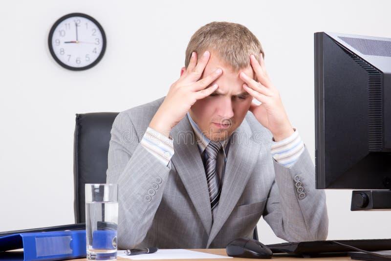 Hombre de negocios cansado joven que se sienta en oficina foto de archivo