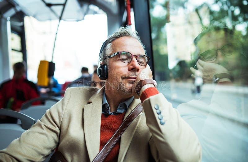 Hombre de negocios cansado maduro con los heaphones que viajan en autobús en ciudad fotografía de archivo libre de regalías