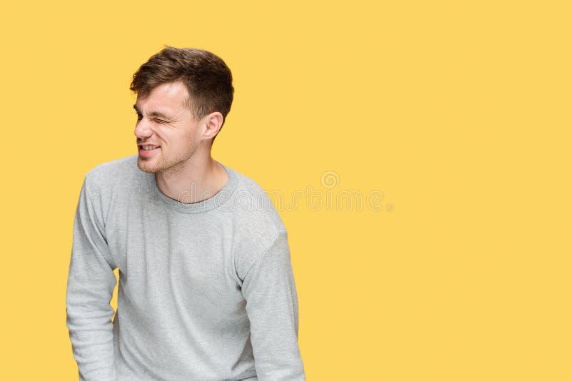 Hombre de negocios cansado o el hombre joven serio sobre fondo amarillo del estudio con dolor imágenes de archivo libres de regalías