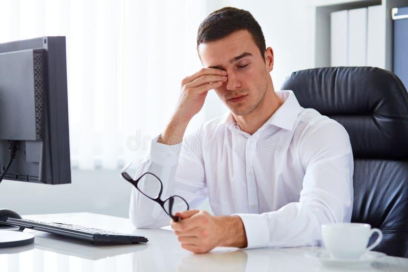 Hombre de negocios cansado que frota el suyo ojo imagenes de archivo