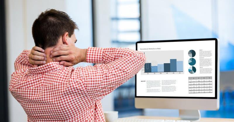 Hombre de negocios cansado que mira gráficos en PC de sobremesa mientras que trabaja la oficina fotos de archivo libres de regalías