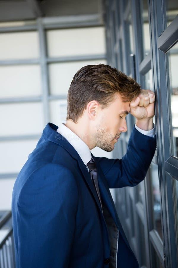 Hombre de negocios cansado que se inclina en puerta imágenes de archivo libres de regalías