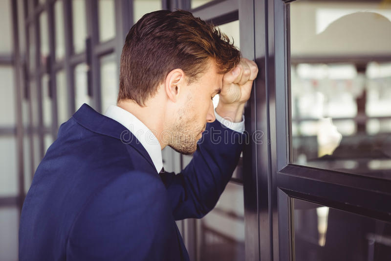 Hombre de negocios cansado que se inclina en puerta fotos de archivo