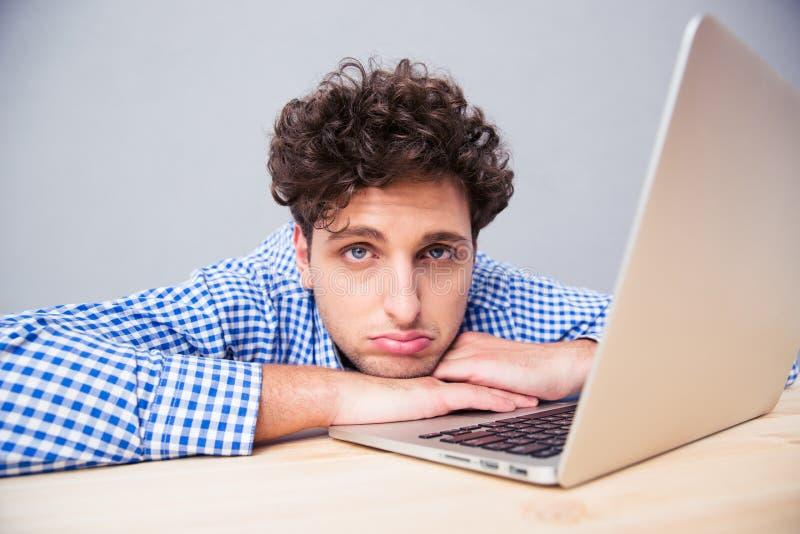 Hombre de negocios cansado que se sienta en la tabla con el ordenador portátil imagen de archivo libre de regalías