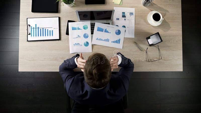 Hombre de negocios cansado que se sienta en la tabla en la oficina, pensando en proyecto, visión superior imagen de archivo libre de regalías