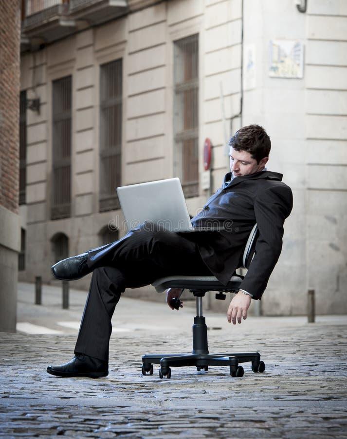 Hombre de negocios cansado que se sienta en silla de la oficina en dormir de la calle imagen de archivo