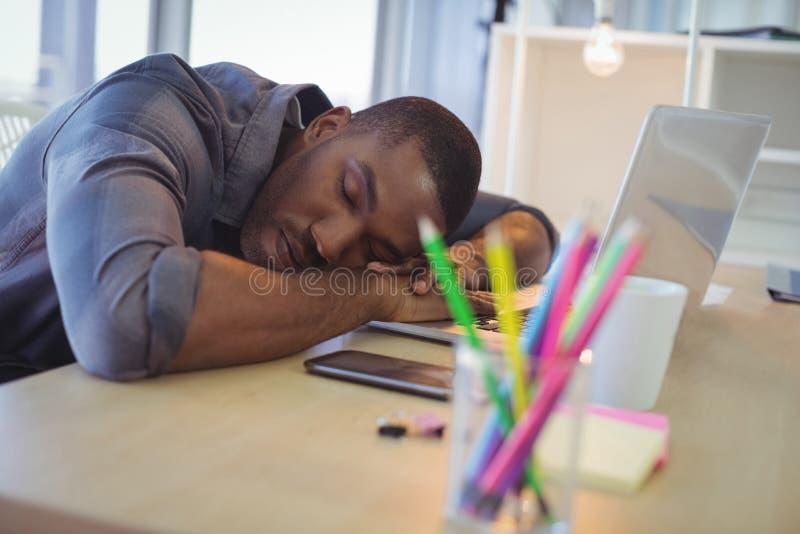 Hombre de negocios cansado que toma una siesta en oficina foto de archivo