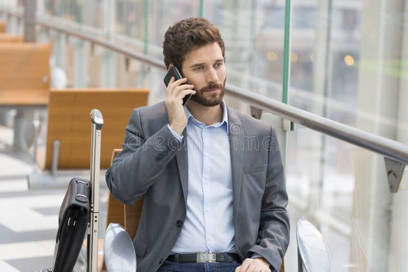 Hombre de negocios casual en el teléfono celular en aeropuerto del pasillo avión que espera imágenes de archivo libres de regalías