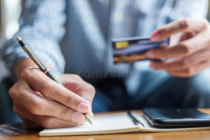 Hombre de negocios casual joven que escribe algo en el cuaderno mientras que sostiene la tarjeta de crédito y con smartphone de l fotografía de archivo libre de regalías