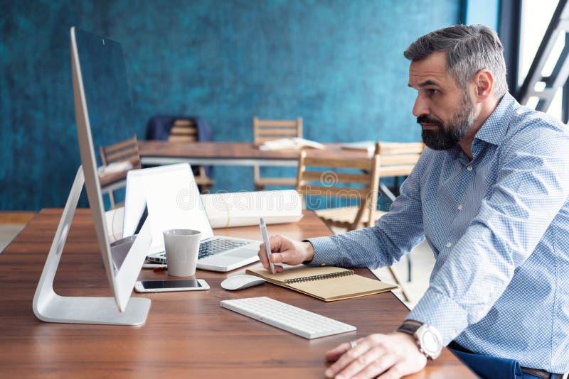 Hombre de negocios casual maduro que usa el ordenador en su escritorio en una oficina moderna imagen de archivo libre de regalías