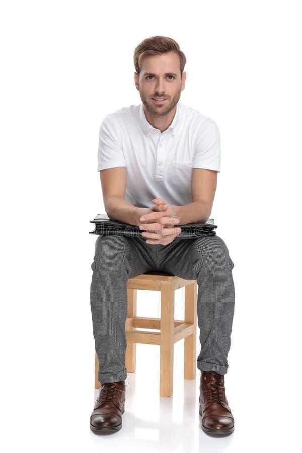 Hombre de negocios casual que descansa sobre silla con los codos en su cartera foto de archivo