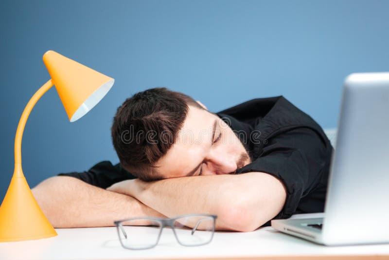 Hombre de negocios casual que duerme en la tabla foto de archivo libre de regalías