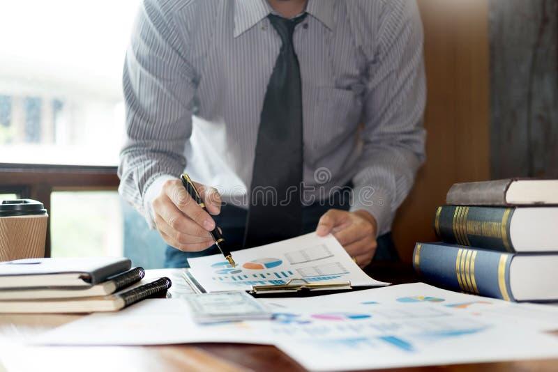 Hombre de negocios casual que se sienta en su funcionamiento en l?nea del escritorio en la oficina con los nuevos documentos de l imagenes de archivo