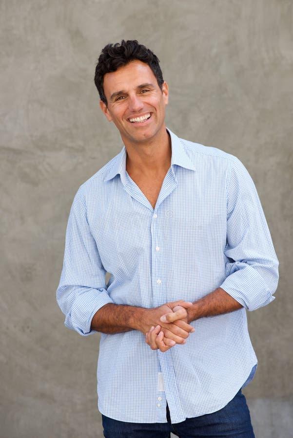 Hombre de negocios casual que sonríe contra la pared fotos de archivo
