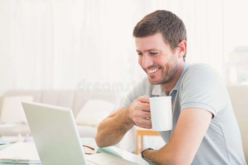 Hombre de negocios casual que sostiene una taza en el escritorio foto de archivo libre de regalías