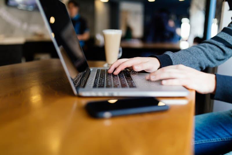 Hombre de negocios casual que trabaja en el ordenador portátil con el libro, el cuaderno, el smartphone móvil y la taza de café e foto de archivo
