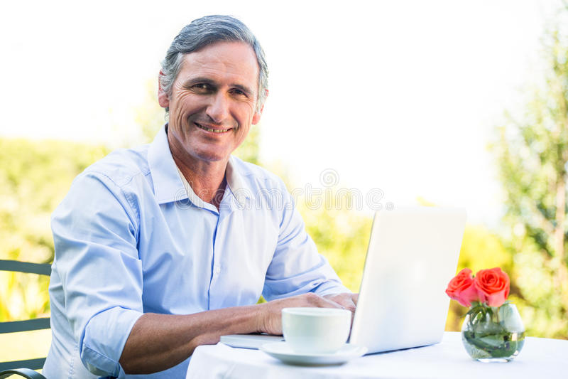 Hombre de negocios casual usando el ordenador portátil y el café el tener fotos de archivo