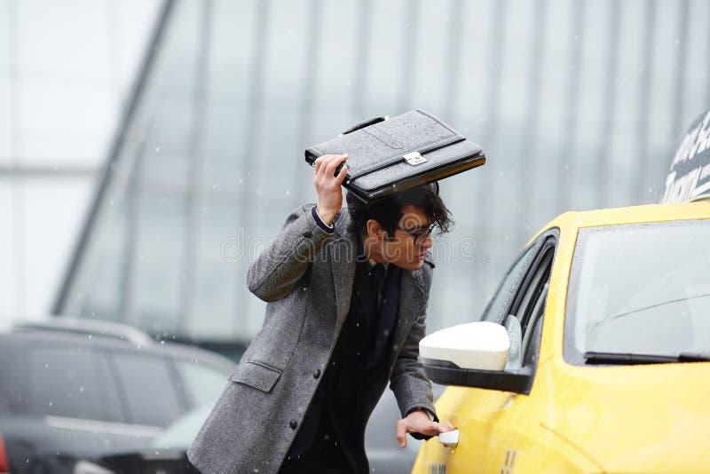 Hombre de negocios Catching Taxi en tormenta imagen de archivo
