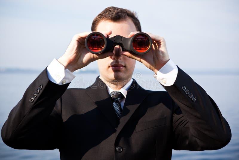 Hombre de negocios caucásico con los prismáticos foto de archivo