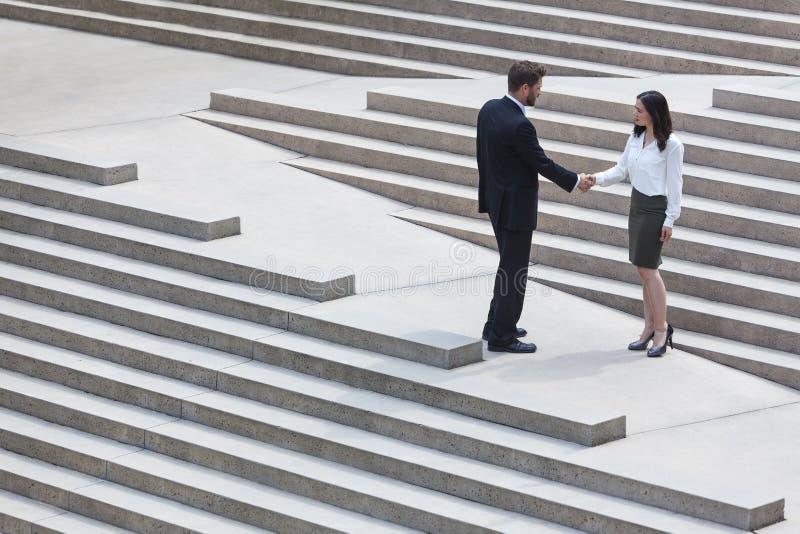 Hombre de negocios caucásico Handshake City Steps de la mujer asiática imagen de archivo