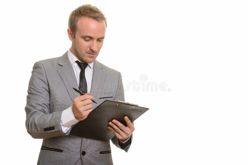 Hombre de negocios caucásico hermoso que escribe en el tablero aislado contra el fondo blanco foto de archivo