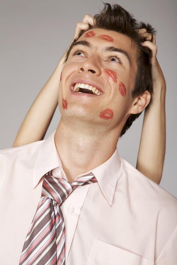 Hombre de negocios caucásico joven con la marca del beso del lápiz labial en su mejilla imagenes de archivo