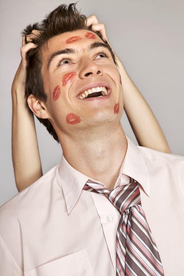 Hombre de negocios caucásico joven con la marca del beso del lápiz labial en su mejilla imágenes de archivo libres de regalías