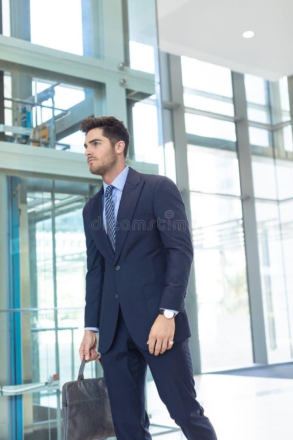 Hombre de negocios caucásico joven que sonríe en la cámara mientras que se coloca en oficina moderna imágenes de archivo libres de regalías
