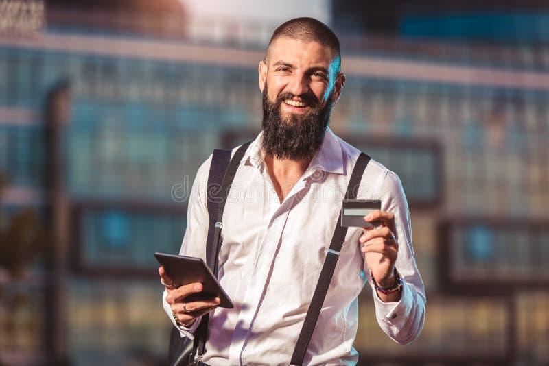 Hombre de negocios caucásico joven que sostiene una tableta y una tarjeta de crédito imagen de archivo