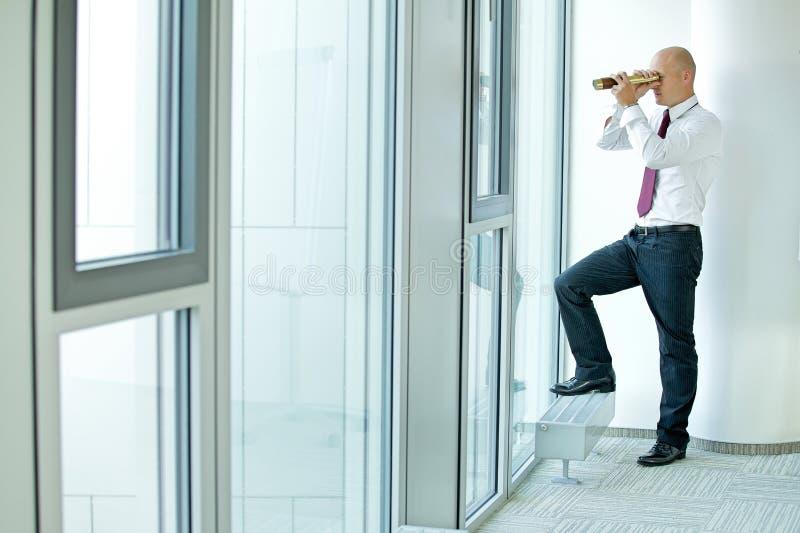 hombre de negocios caucásico que espía usando el telescopio a través de ventana de la oficina imagenes de archivo