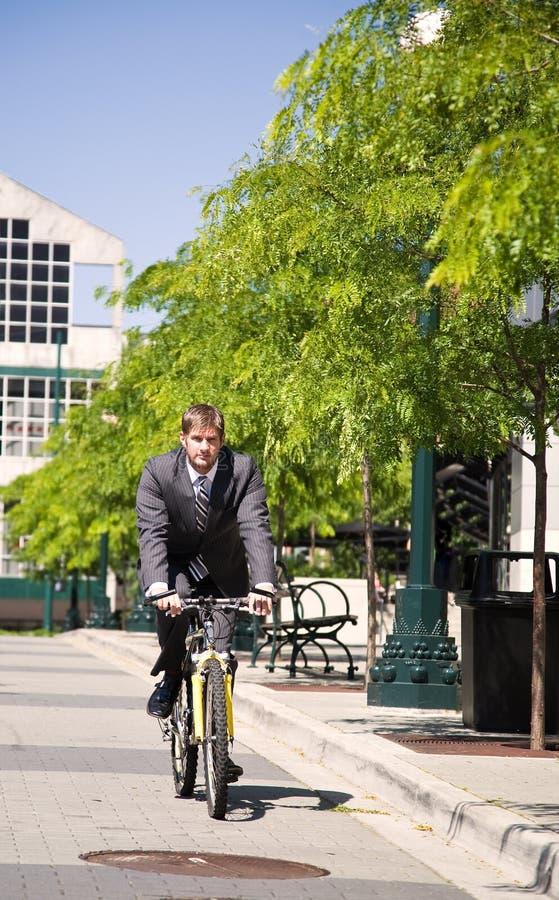 Hombre de negocios caucásico que monta una bicicleta imagen de archivo