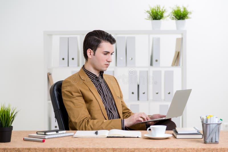 Hombre de negocios caucásico usando el ordenador portátil foto de archivo libre de regalías