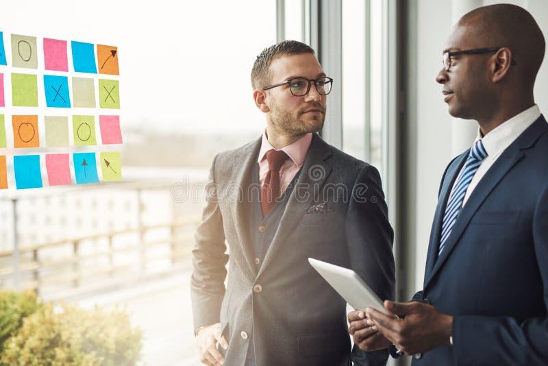 Hombre de negocios caucásico y africano en una reunión imagen de archivo libre de regalías