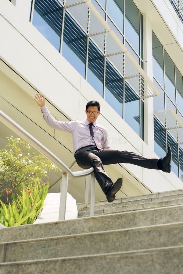 Hombre de negocios chino feliz Going Downstairs Sliding en el carril fotografía de archivo