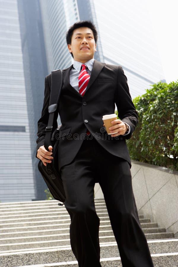 Hombre de negocios chino que acomete abajo de pasos de progresión foto de archivo libre de regalías