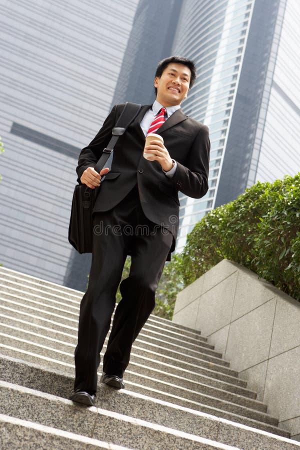 Hombre de negocios chino que acomete abajo de pasos de progresión imagen de archivo libre de regalías