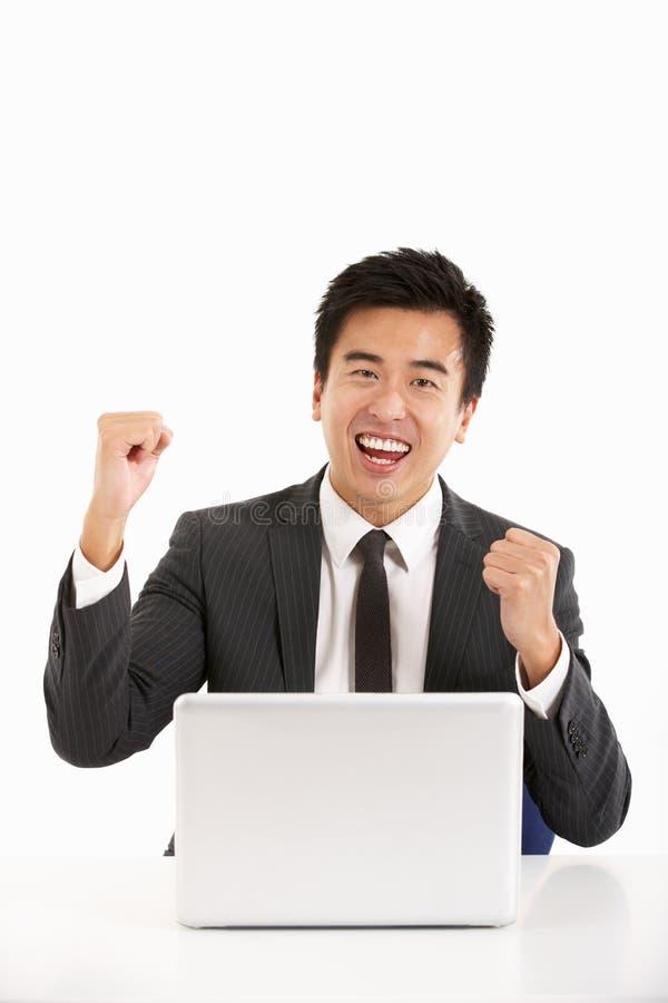 Hombre de negocios chino que trabaja en la computadora portátil y Celebra foto de archivo
