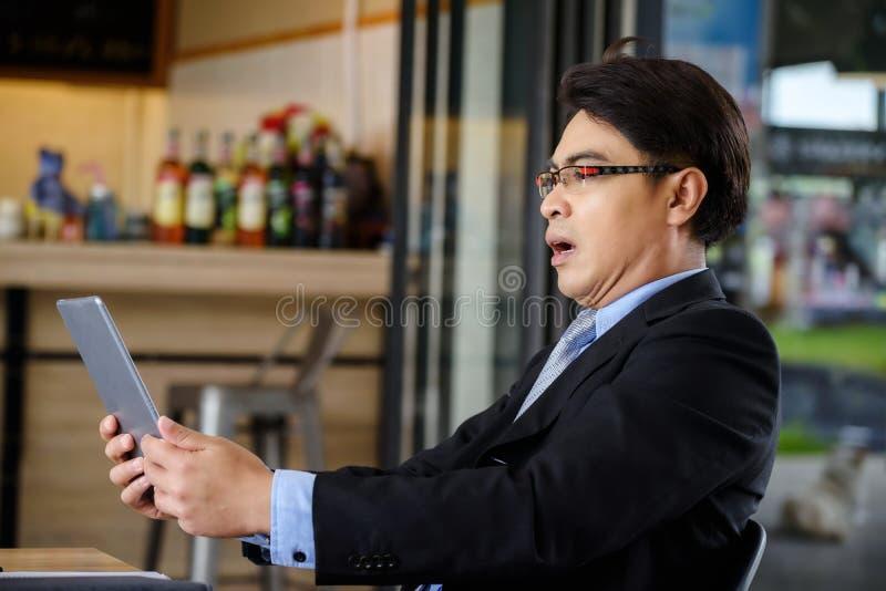 Hombre de negocios chocado después de noticias leídas en la tableta fotografía de archivo libre de regalías