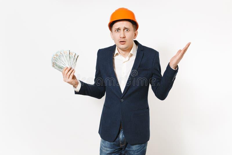 Hombre de negocios chocado hermoso joven en el traje oscuro, paquete protector de dólares, dinero de la tenencia del casco de la  imagen de archivo