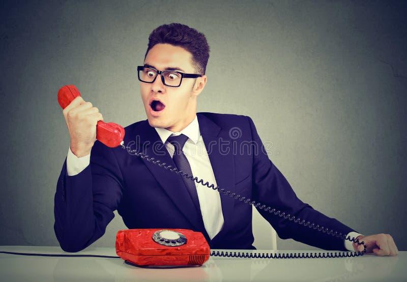 Hombre de negocios chocado que recibe malas noticias en el teléfono que se sienta en el escritorio en su oficina fotos de archivo libres de regalías