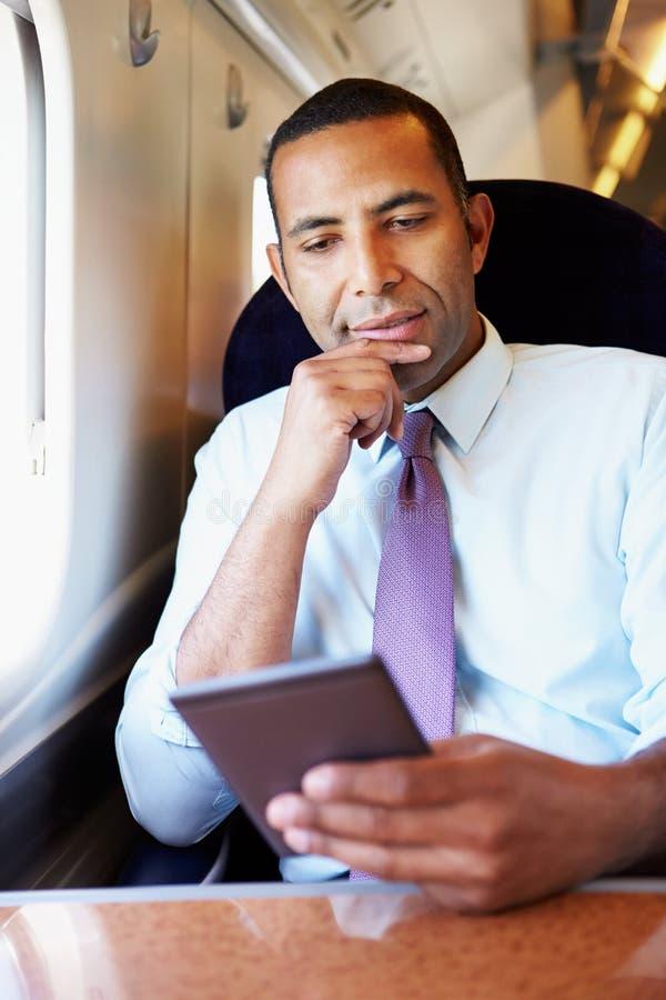 Hombre de negocios Commuting On Train que lee un libro fotos de archivo