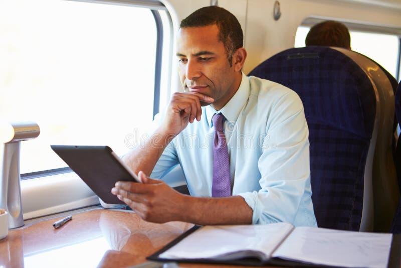 Hombre de negocios Commuting On Train que usa la tableta de Digitaces imagenes de archivo