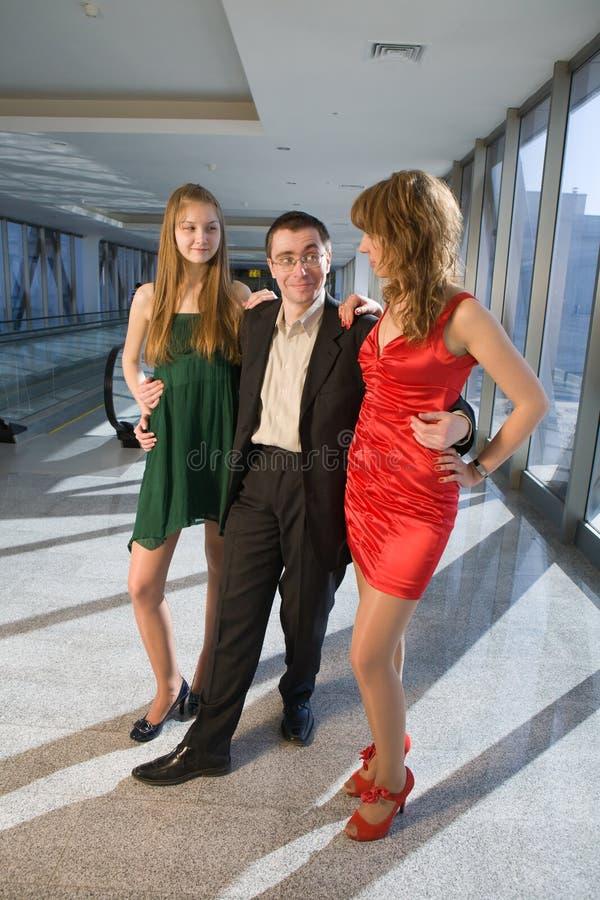 Hombre de negocios con dos muchachas imagen de archivo