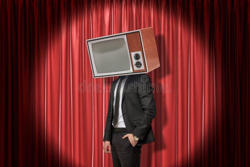 Hombre de negocios con el aparato de TV del vintage en vez de la cabeza en fondo rojo de las cortinas de la etapa foto de archivo libre de regalías