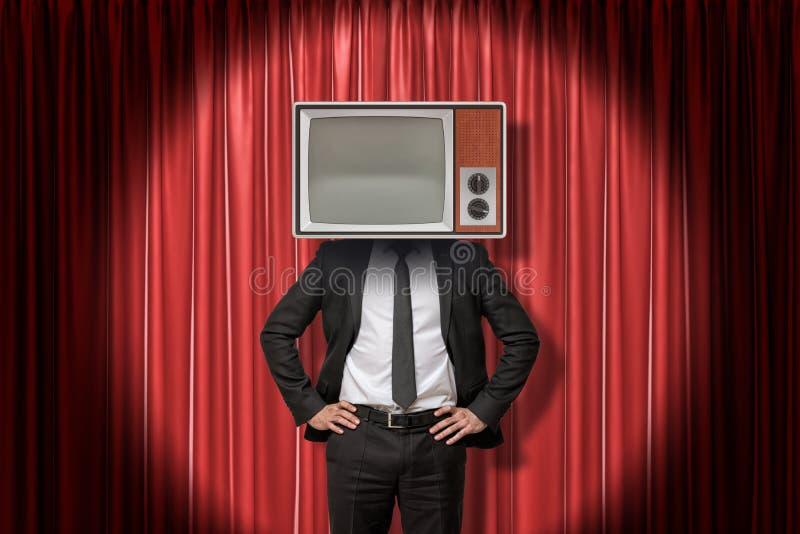 Hombre de negocios con el aparato de TV del vintage en vez de la cabeza en fondo rojo de las cortinas de la etapa fotos de archivo