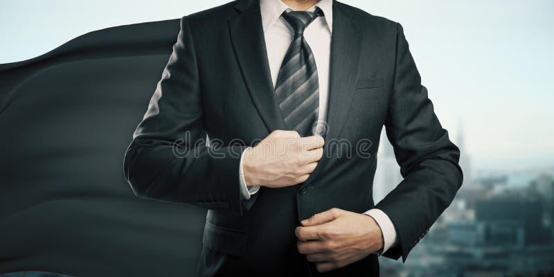 Hombre de negocios con el cabo negro del super héroe foto de archivo